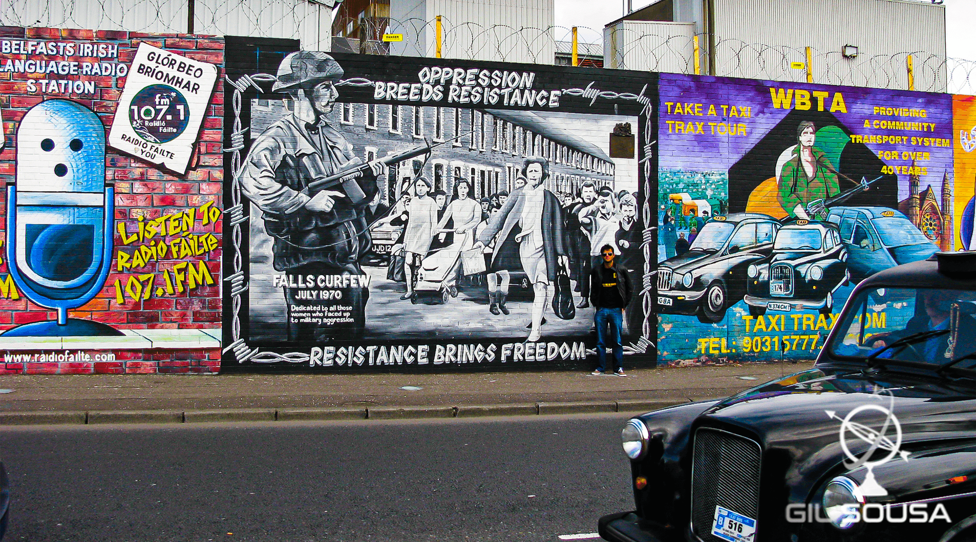 Back taxi next to one of the Peace Wall's section in Belfast
